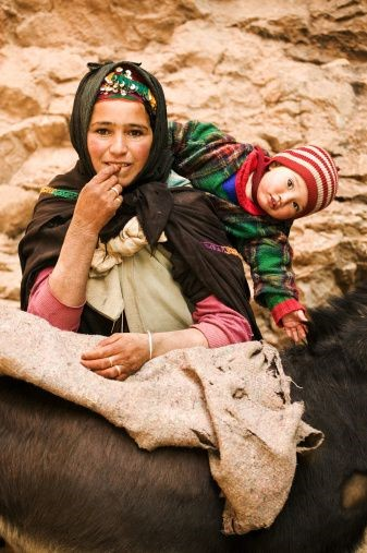 A Berber nomad woman with her child takes a break from loading her ...